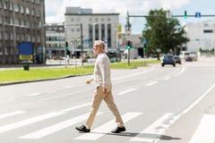 Senior man walking along city crosswalk Royalty Free Stock Photography
