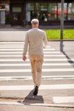 Senior man walking along city crosswalk Royalty Free Stock Images
