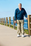 Senior Man Walking Along Path By The Sea Stock Images