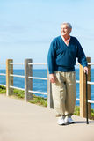 Senior Man Walking Along Path By The Sea Royalty Free Stock Photos