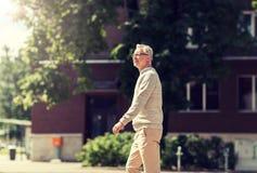 Senior man walking along summer city street royalty free stock image