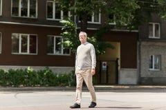 Senior man walking along summer city street Stock Photo
