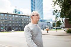 Senior man walking along summer city street Stock Images