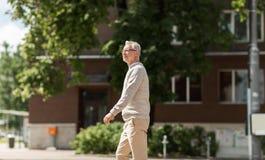 Senior man walking along summer city street Stock Photography