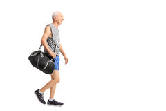 Senior man walking and carrying a sports bag Stock Image