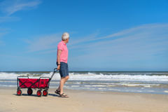 Senior man walking with cart at the beach Royalty Free Stock Photography