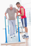 Senior man walking with coach help Royalty Free Stock Photos
