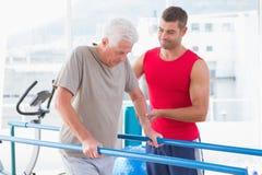 Senior man walking with coach help. Senior men walking with coach help in fitness studio Royalty Free Stock Photos