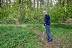 Senior man walking with crutches. Mature man walking with the aid of crutches in woodland Stock Photos