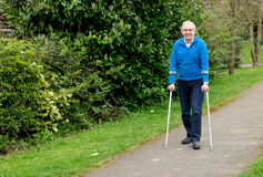 Senior man walking with crutches. Mature man walking in park with aid of crutches Royalty Free Stock Photos