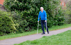 Senior man walking with crutches. Mature man walking in park with aid of crutches Royalty Free Stock Image