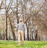 Senior man walking with crutches in park. Rear view shot with tilt and shift lens Royalty Free Stock Photos