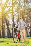 Senior man walking with his bike outdoors Royalty Free Stock Images