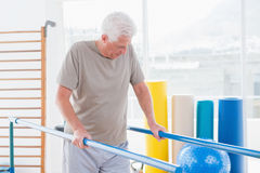 Senior man walking with parallel bars Stock Photography