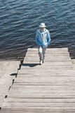 Senior man walking by pavement on the riverside at daytime. Stylish senior man walking by pavement on the riverside at daytime Royalty Free Stock Photos