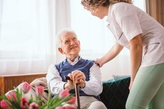Senior man with a walking stick being comforted by nurse in the hospice stock images