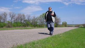 Senior man with walking stick hikes on a country road stock video footage