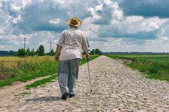 Senior man with walking stick wearing straw hat goes home on a cobblestone road Stock Photo