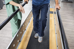 Senior Man Walking With Support Of Bars By Female Physiotherapis. Low section of senior men walking with support of bars by female physiotherapist in fitness Royalty Free Stock Photo