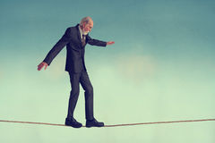 Senior man walking a tightrope Royalty Free Stock Photos