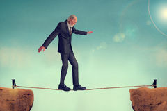 Senior man walking a tightrope Stock Photo