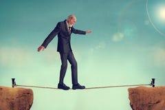 Senior man walking a tightrope stock photo