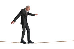 Senior man walking a tightrope Royalty Free Stock Images