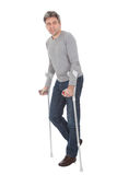 Senior man walking using crutches. Isolated on white Royalty Free Stock Images