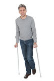 Senior man walking using crutches. Isolated on white Stock Photos