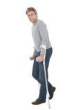 Senior man walking using crutches Stock Photos