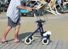 Senior man walking with Walker on the beach in summer Stock Photos