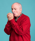 Senior man warming up cold hands. On a blue background Royalty Free Stock Photography