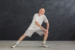Senior man warmup stretching training indoors. Senior fitness man warmup training indoors. Sporty mature guy makes aerobics exercise, stretching legs. Active Stock Images