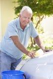 Senior Man Washing Car In Drive Royalty Free Stock Image