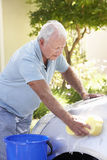 Senior Man Washing Car In Drive Royalty Free Stock Images