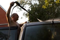 Senior man washing car. With high pressure washer Royalty Free Stock Photography