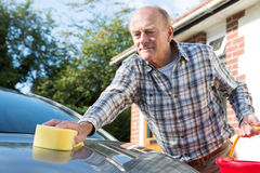 Senior Man Washing Car With Sponge Stock Photos