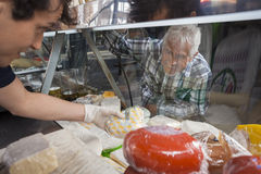 Senior Man Watching Salesman Picking Cheese From Display Cabinet Royalty Free Stock Photography