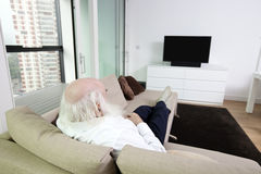 Senior man watching television in apartment Stock Photo