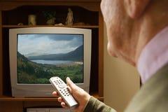 Senior man watching television. Senior men watching television Stock Photos