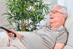 Senior man watching tv. Elderly retired man sitting sofa at home. Retirement concept Royalty Free Stock Image
