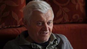 Senior man watching TV. HD 1080 Static: senior man watching tv, smiling and looking around stock footage