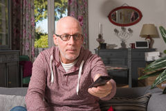A senior man watching tv in her sofa. Senior on a sofa in his home watch tv Stock Images