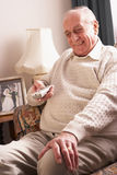Senior Man Watching TV At Home. Smiling Stock Photo
