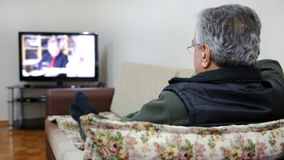 Senior man watching TV. Show while sitting on sofa in his living room royalty free stock photo