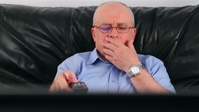 Senior man watching TV on sofa at home Royalty Free Stock Photos