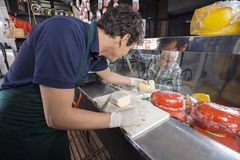 Senior Man Watching Worker Picking Cheese From Display Cabinet royalty free stock photo