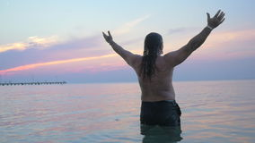 Senior man in water stretching hands stock footage