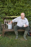 Senior man with watering can on bench, portrait Royalty Free Stock Photo
