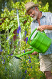 Senior man with a watering can Stock Photos